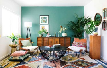 Living room with green accent wall, boho chairs, credenza, plants, rug, coffee table.