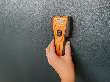 Use a stud finder to locate studs and possible electrical wires hidden behind the spot you want to put your cutout.