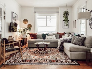 Ecclectic living room with gray couches, oriental rug and a floor lamp.