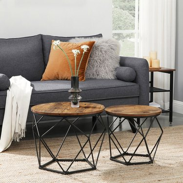 Two small circular nesting tables with geometric metal bases and round wood surfaces