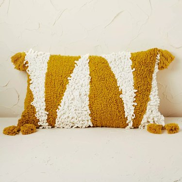 geometric patterned tufted shag pillow in gold and white pattern