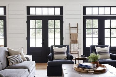 high-contrast living room with white walls and black doors