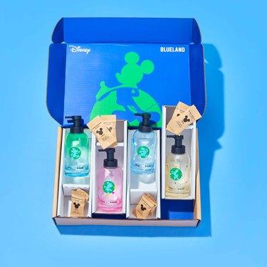 cardboard box holding four disney soap bottles