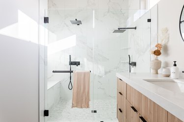Bathroom with shower, two shower heads, wooden vanity.