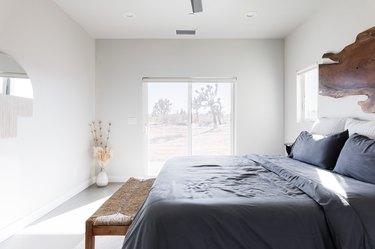 Bed, bench, vase, dried flowers, mirror, sliding glass door.