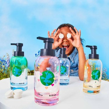 four disney soap bottles in front of a girl holding tablets in front of her eyes