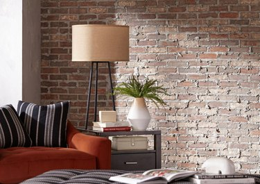 Living room with brick wall, couch, pillows, floor lamp, end table, plant.