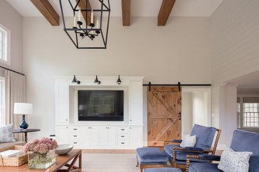 living room with reclaimed wood barn door and beams