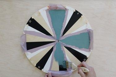 Painting teal chalkboard paint on IKEA kids activity wheel