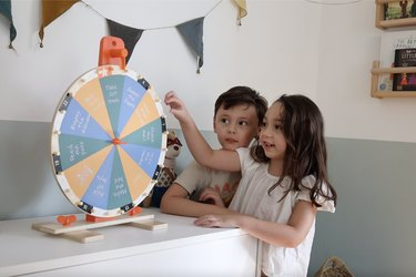 Two kids spinning IKEA activity chore prize wheel