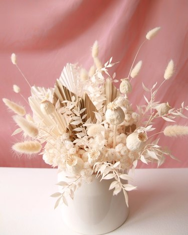 preserved floral arrangement in white vase with pink background