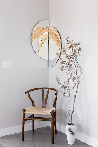Accent chair, mirror, vase, branch.