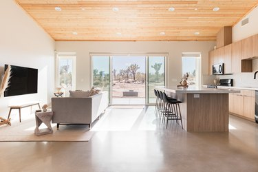 Kitchen and living area with island, bar stools, couch, tv, end table, bench, cabinets, windows, wood ceiling.