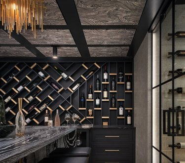 Basement wine cellar with fabric ceiling, wine shelves, bar, chandelier.