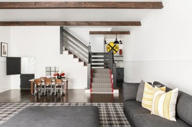 Basement with wood beam ceilings, couch, dining area.