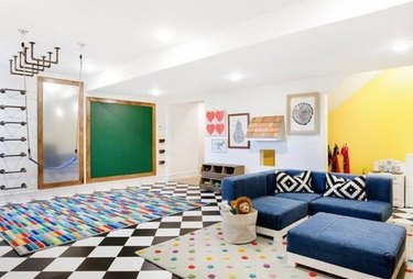 Basement playroom with colorful rugs, couch, recessed lighting.