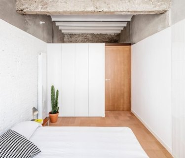 Basement bedroom with concrete ceiling, white walls, wood floor, bed.