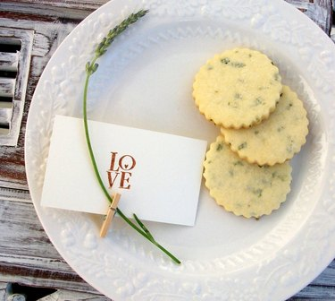 """overhead shot of plate with lavender cookies, greenery, and card that reads """"love"""""""