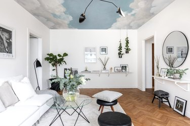 Basement with white walls, mural on ceiling, mirror, couch, chairs.