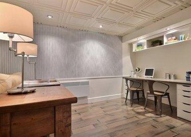 Basement with drop ceiling tiles, wood floor, desk, lamps, chairs.