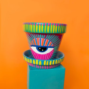 hand-painted pot with bright colors and eye design