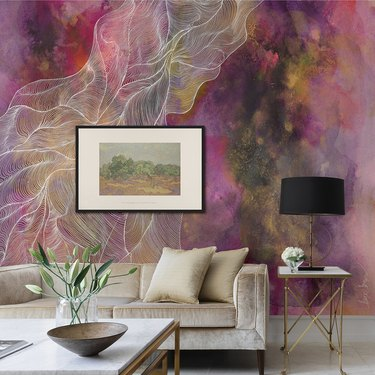 couch near coffee table and side table with black lamp, and framed art on a wall with abstract mural with pink tones and white