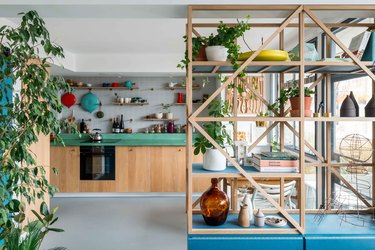 The kitchen of architect Ben Allen's London home featuring shelves and bright blue accents