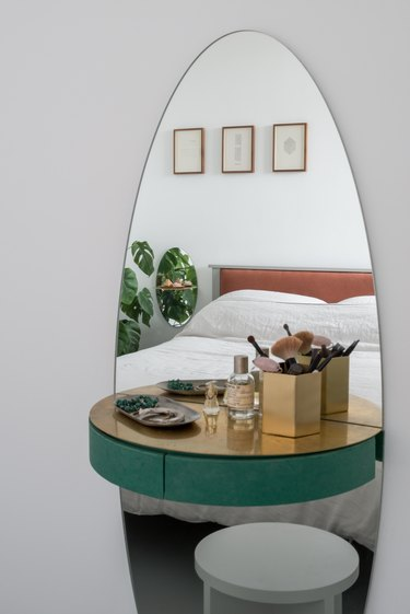 vanity with elliptical mirror, brass shelf, and green drawer