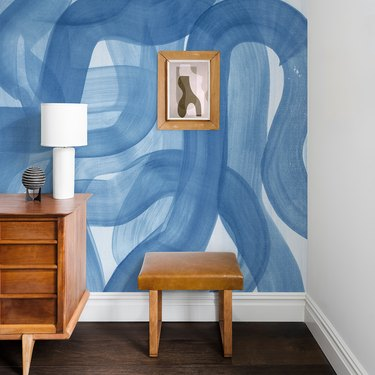 wood dresser, stool, and framed art near a blue and white abstract mural