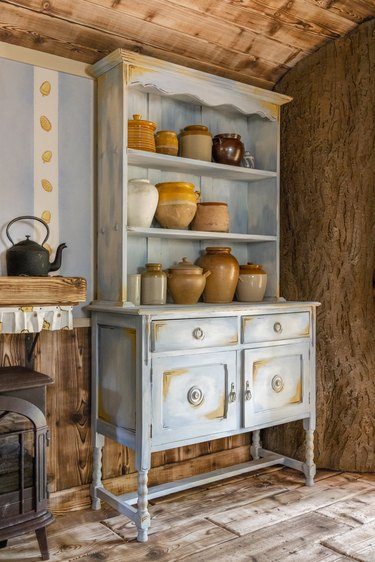 interior of Winnie the Pooh-themed airbnb featuring blue shelves with honey pots