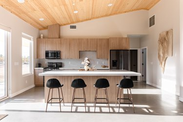 An open kitchen with oak cabinets and a wood ceiling