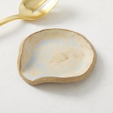 gold spoon near beige spoon rest