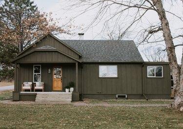 dark green farmhouse exterior with wood door