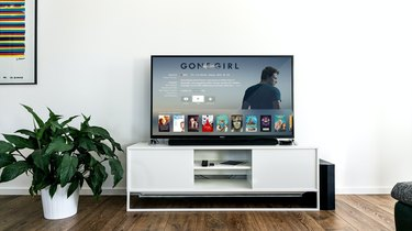 television on white console next to plant