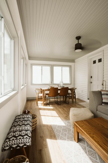 Sunroom with gray shiplap painted ceiling, light wood floors and black ceiling fan.