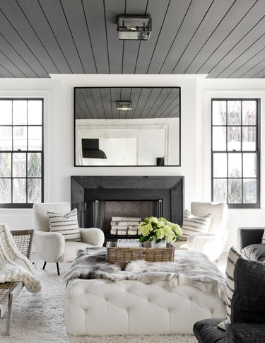Living room with gray painted ceiling with shiplap, fireplace and white couches.