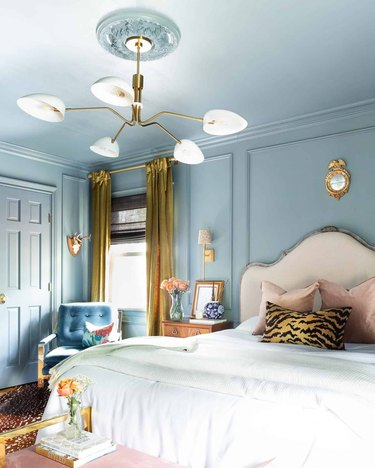 Glam bedroom with monochromatic blue paint and gold accents.