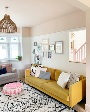 Eclectic living room with beige ceiling paint and yellow couch.