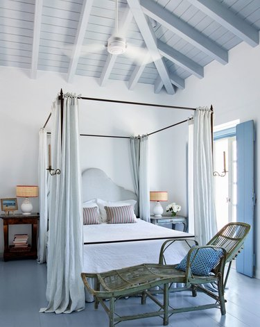 Airy bedroom with blue wood ceiling treatment.
