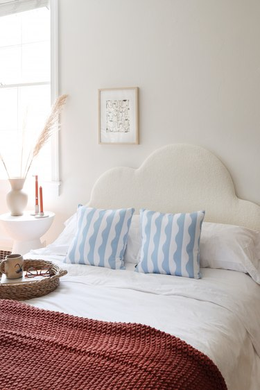 DIY boucle upholstered cloud headboard styled with throw pillows and bedroom accessories