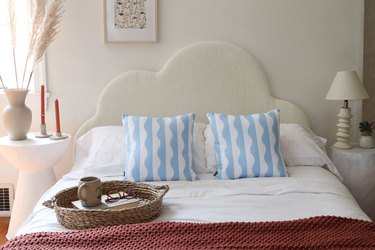 DIY boucle fabric cloud headboard styled with throw pillows and bedroom accessories