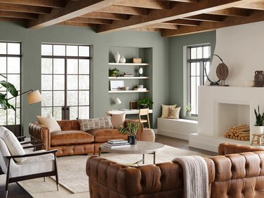 living room with evergreen fog walls and brown leather furniture