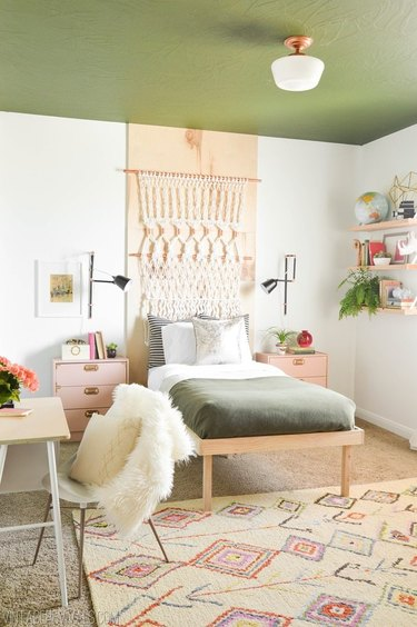 Bedroom with green painted ceiling, macrame wall hanging and black wall sconces.