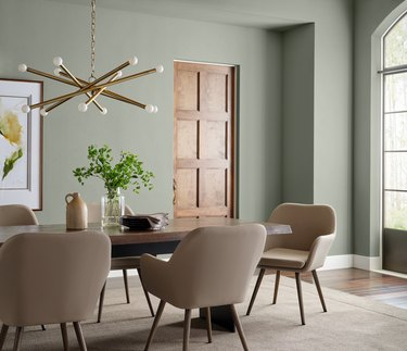 dining room with evergreen walls and sputnik chandelier