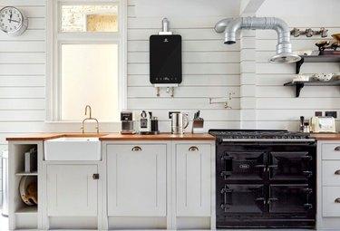 Black LP Tankless Water Heater on Wall in Modern White Kitchen