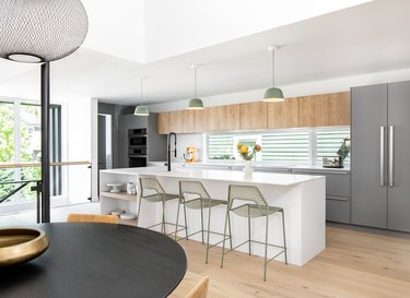 kitchen area with white island with chairs and gray refrigerator