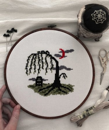 person holding an embroidery hoop with a scene of a weeping willow