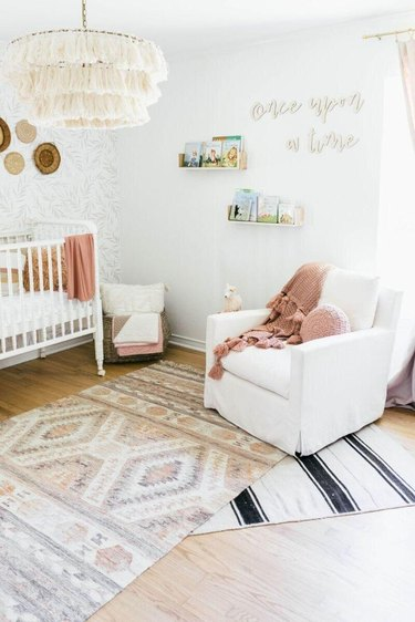 white nursery with layered rugs in different patterns