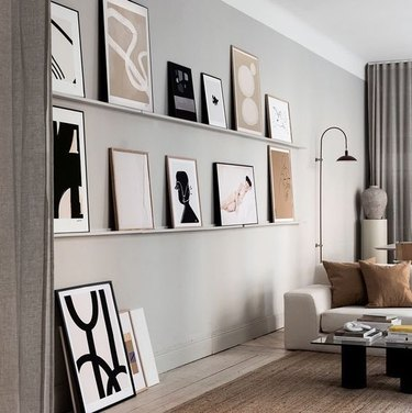 picture ledges with leaning artwork in living room