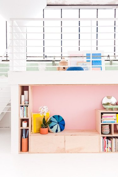 pink accent wall in reading nook in white room